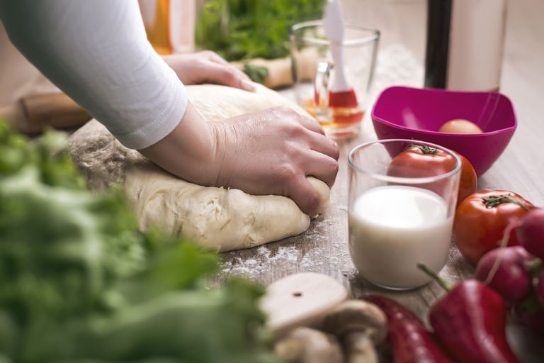 woman kneading bread dough on table with fresh vegetables around