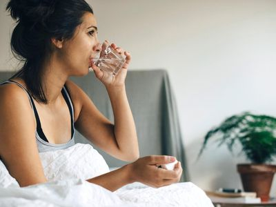 young women taking pill with water