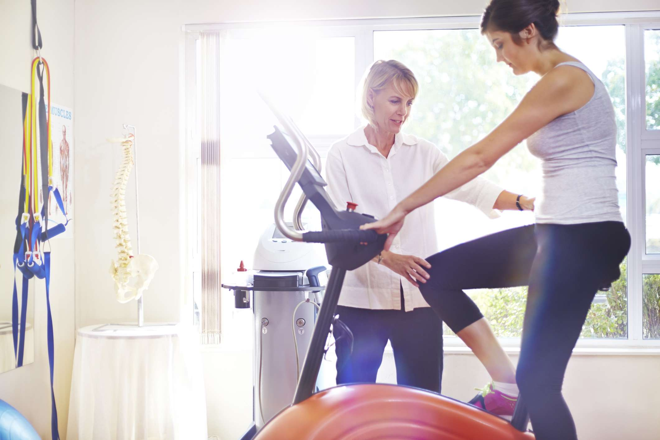 woman on stationary bike with physical therapist giving advice