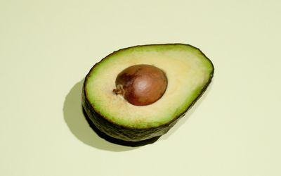 A close up of half of an avocado on a pale green background.