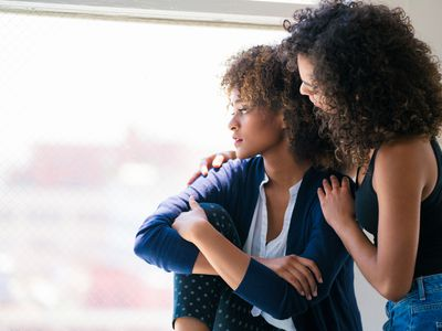 young woman feeling sad and her friend consoling her