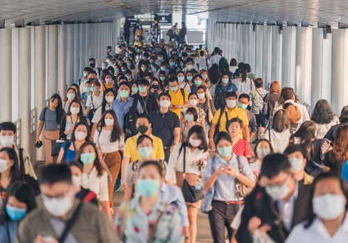 People in crowded terminal wearing face masks
