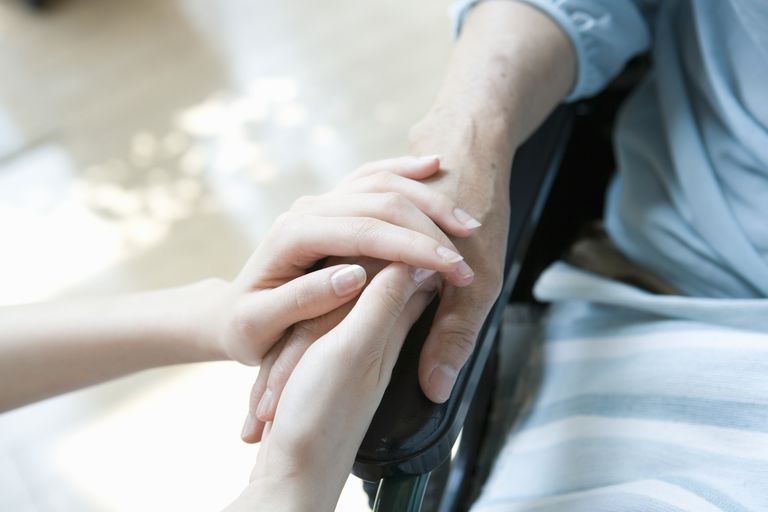 Woman holding hands of patient in wheelchair