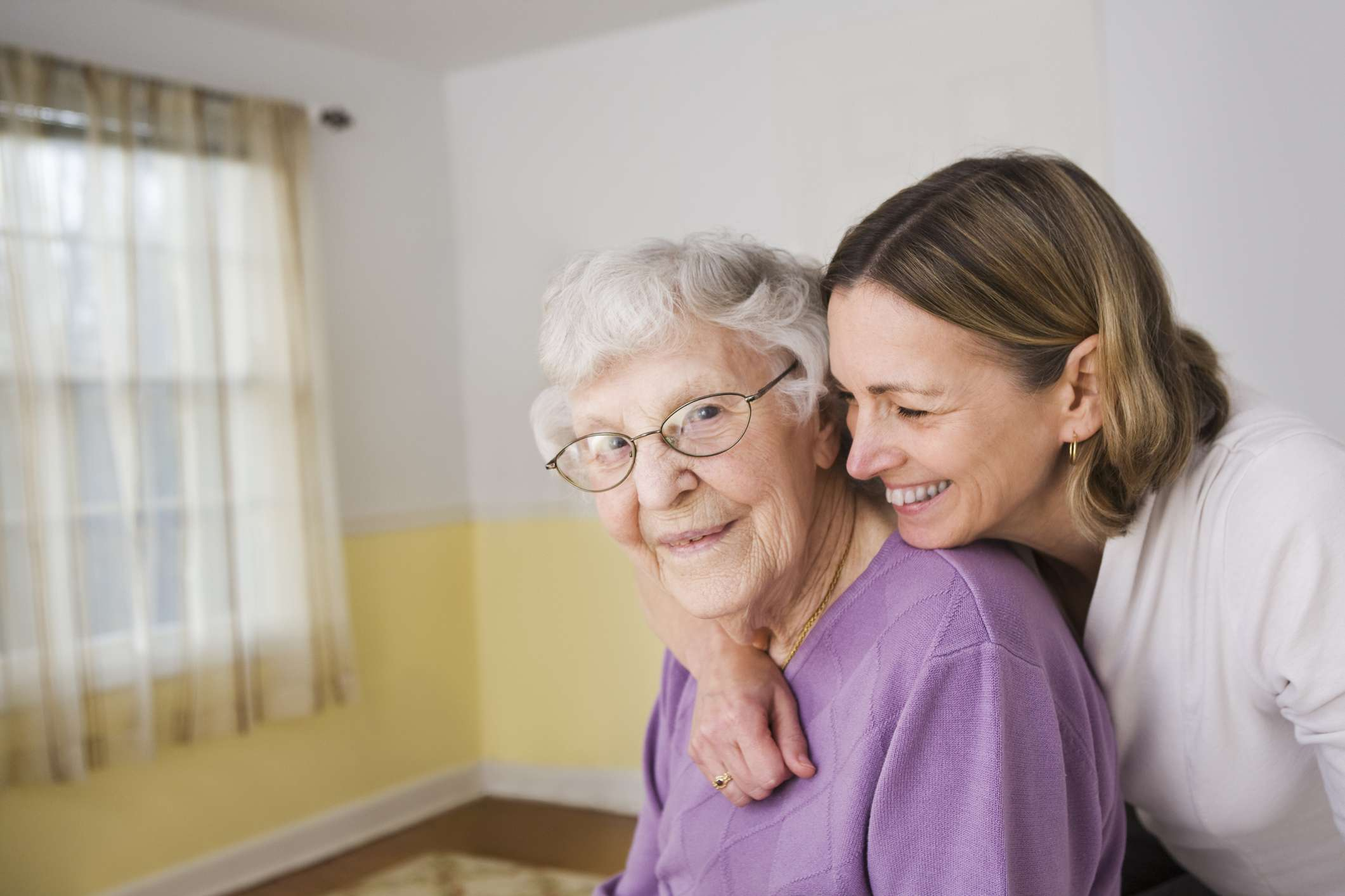 daughter caring for elderly mom and smiling