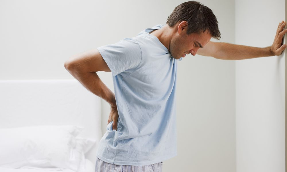 Man in discomfort leaning over holding his back