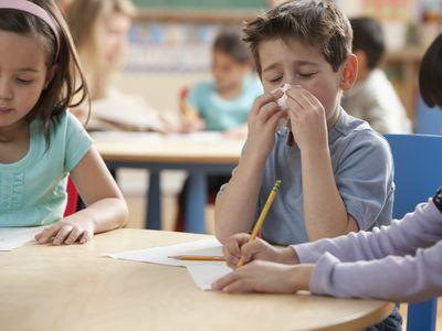 boy sneezing in classroom