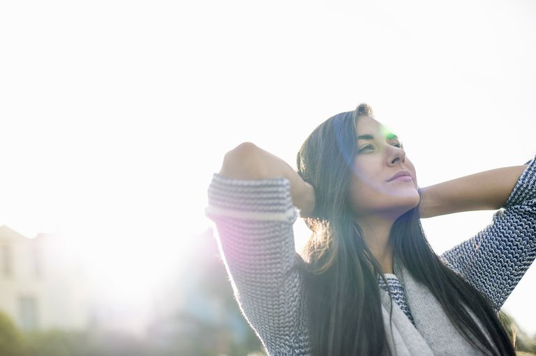 Hopeful woman with hands behind head in sunlight
