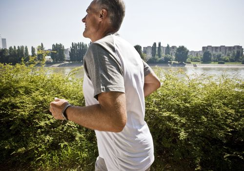 An older gentleman running in front of a lake