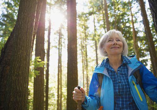 Smiling woman hiking through trees