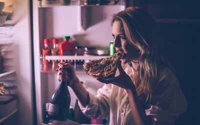 Woman eating pizza and drinking wine in front of the refrigerator during the night