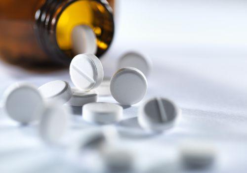 white pills spilling from a bottle