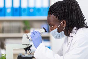 Female laboratory worker using microscope