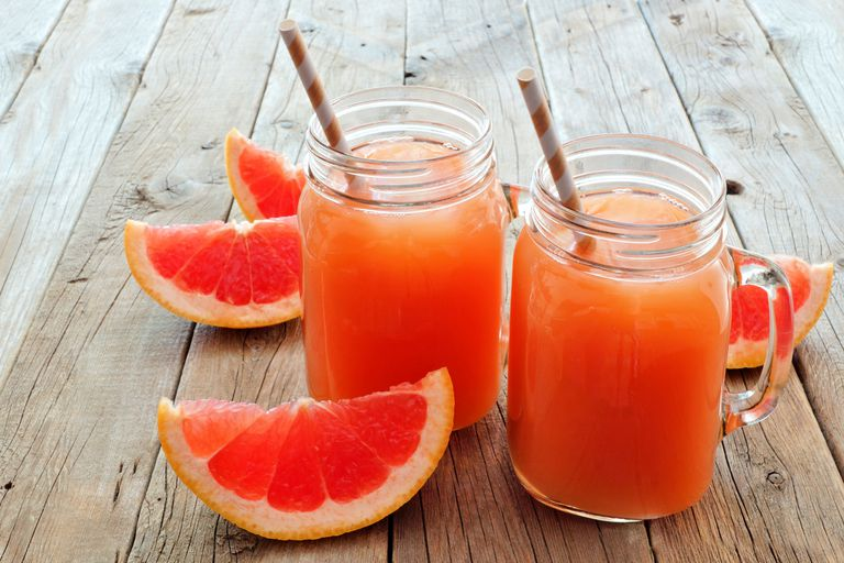 Two glasses of grapefruit juice surrounded by grapefruit slices