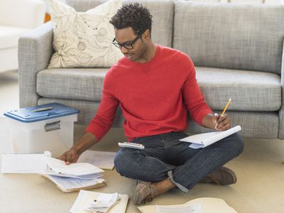 man on floor with tax forms