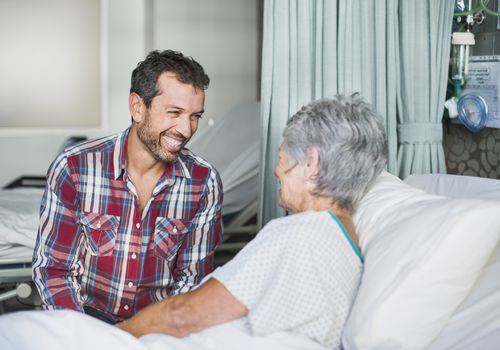 Man visiting with senior woman in the hospital