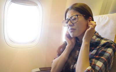 A woman trying to pop her hers on a plane