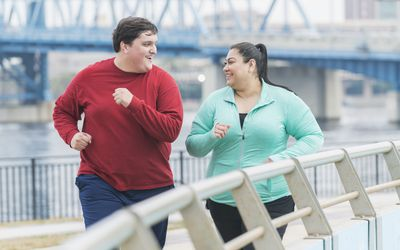 Man and woman smiling and working out together