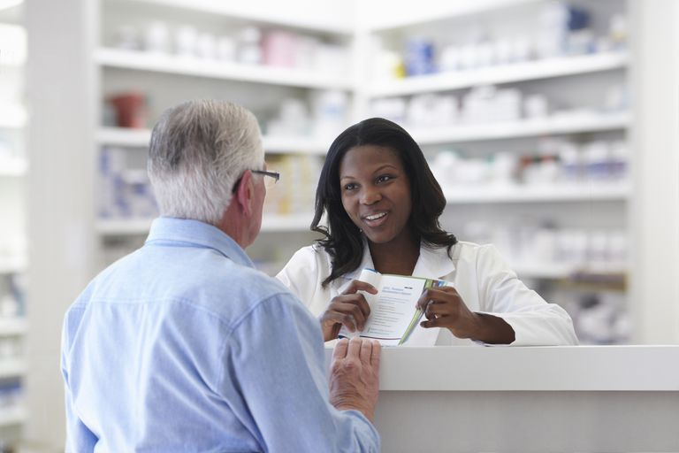 Pharmacist talking to man about his medication