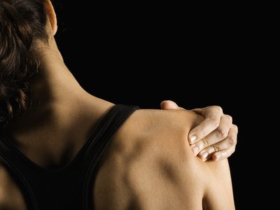 a woman pressing on a shoulder trigger point.