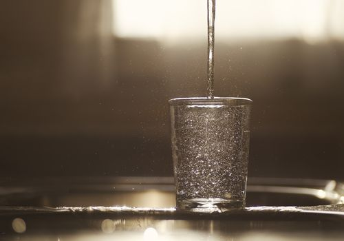 Glass of water being poured.