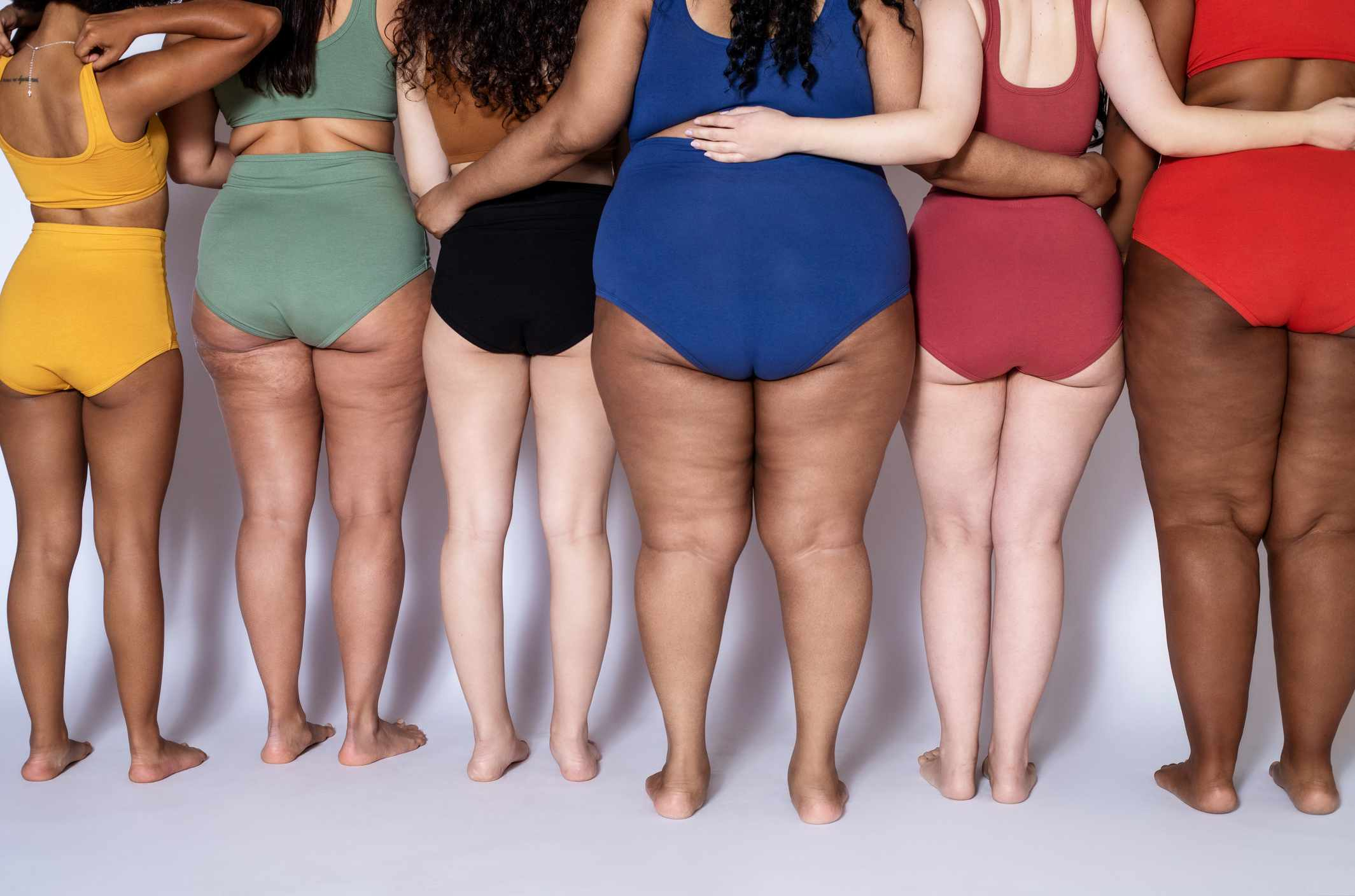 Rear view of group of women with different body types in underwear standing together on white background.
