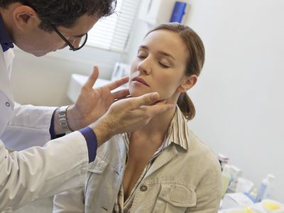 Doctor palpating woman's lymph node