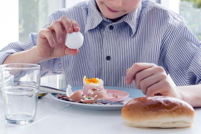 Child sprinkle salt on egg
