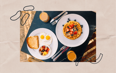 Breakfast foods like waffles and eggs on a table.