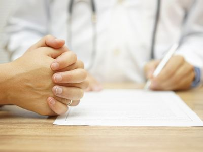 concerned woman next to doctor writing