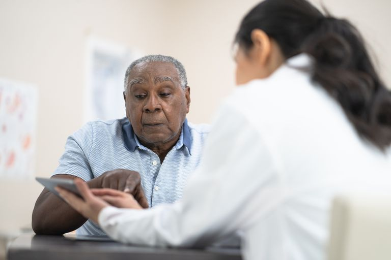 Doctor showing information to a senior man