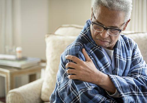 Man rubbing his sore shoulder