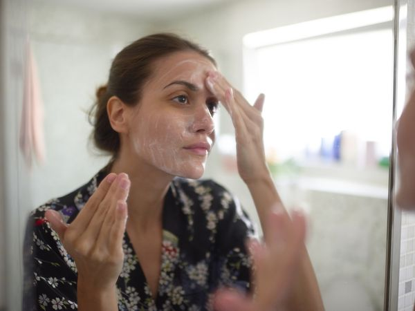 Woman washing face in mirror