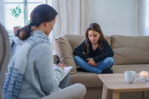 Sad and depressed small girl with therapist sitting indoors, psychotherapy. - stock photo