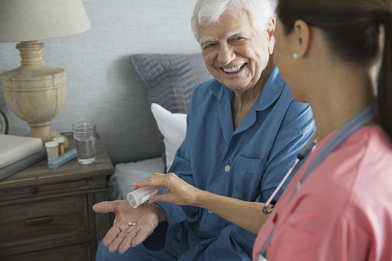 Home care nurse giving pills to senior man in bedroom