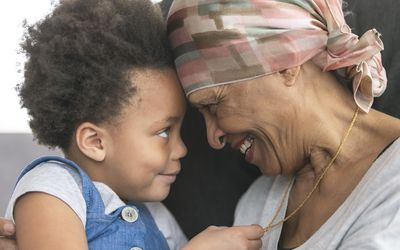 A black woman with cancer is wearing a scarf on her head. She is sitting in a lounge chair with her young granddaughter. The two are embracing and their foreheads are touching. They are looking at each other and smiling. The girl is holding her grandmother's necklace.