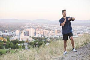 Mixed race man checking pulse on hilltop over Salt Lake City, Utah, United States