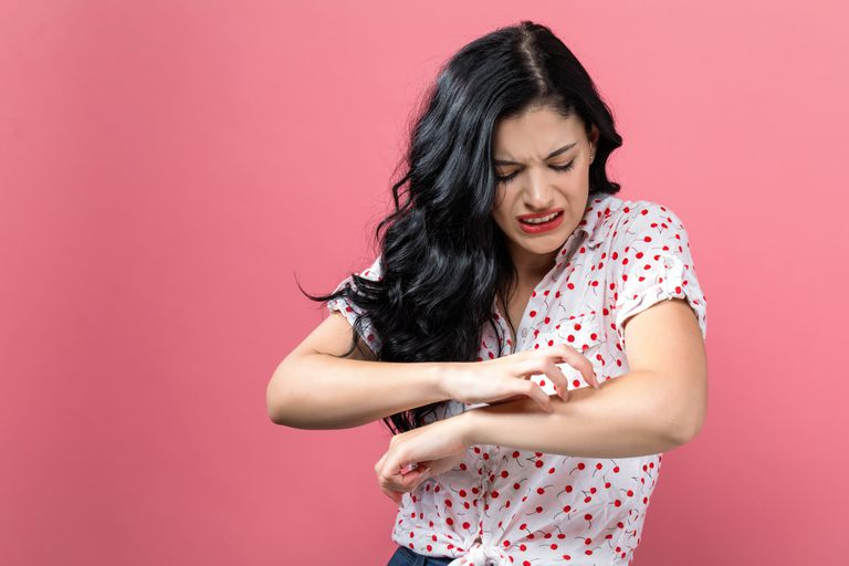 Young Woman Scratching her Itchy Arm