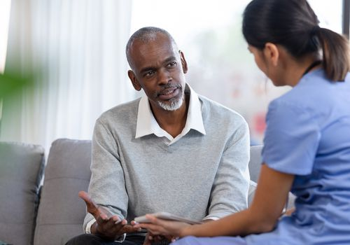 Senior man gestures while speaking with a healthcare provider.