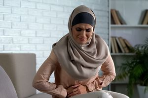 Young muslim woman with a stomach ache.