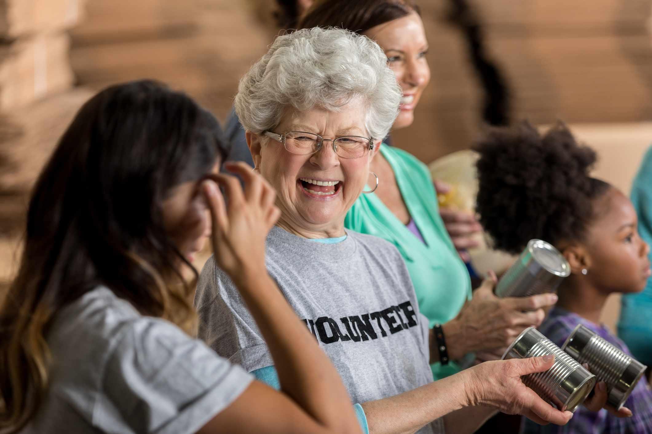7568ac2e4bb Laughing senior woman wearing a volunteer shirt at a food drive