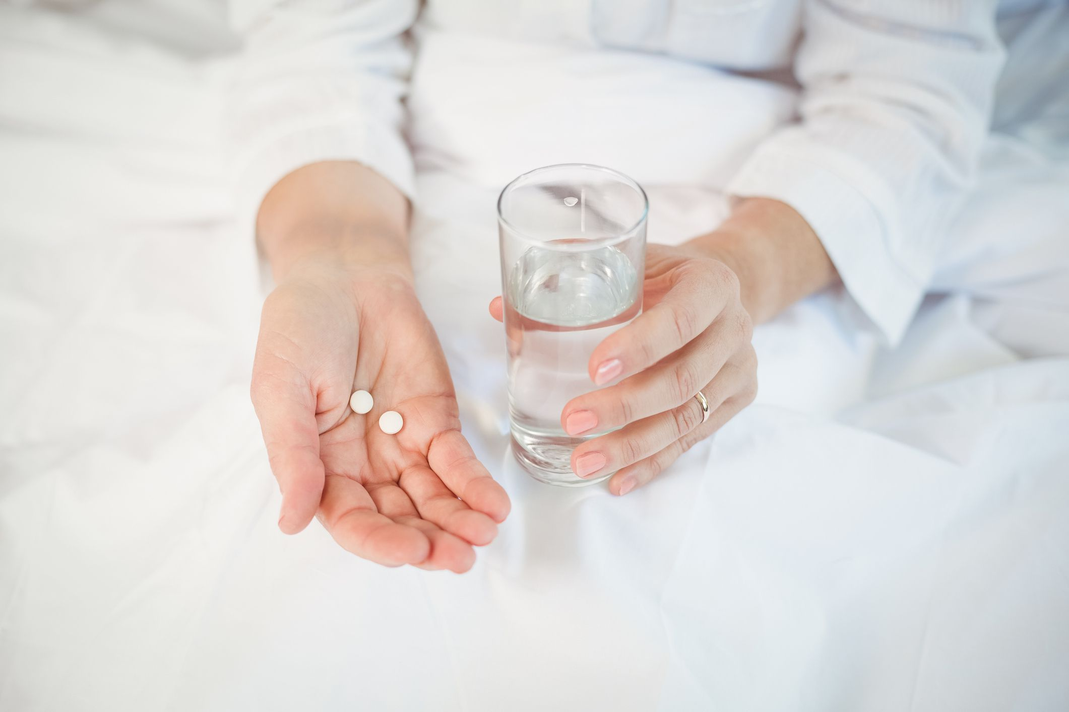 woman in bed taking medication with water