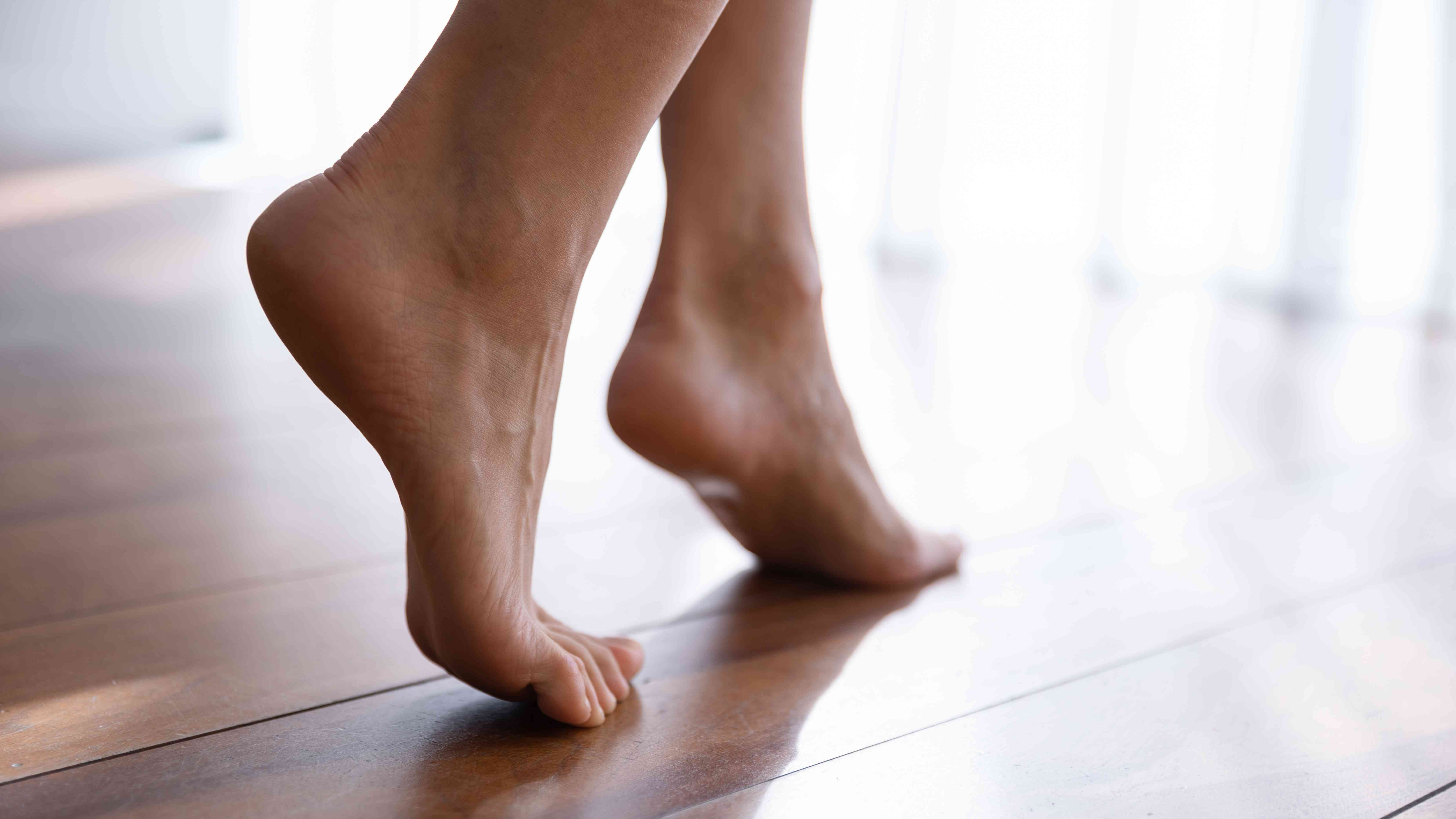 Close up side view beautiful female feet on wooden floor