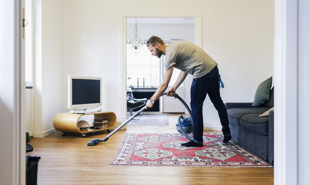 Side view of man vacuuming hardwood floor