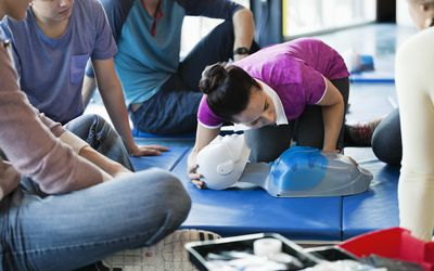 Instructor teaching CPR to class in fitness center
