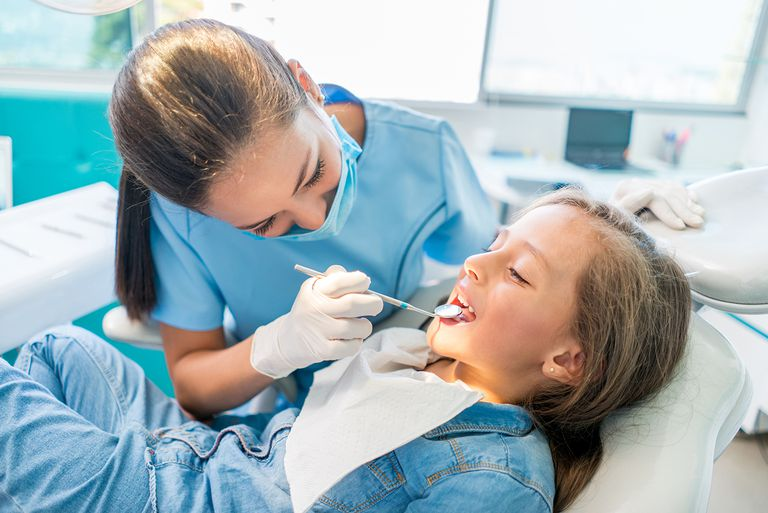 Beautiful girl at the dentist getting a check up on her teeth