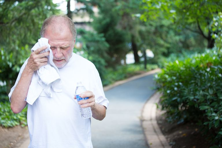Man wiping sweat from his head while walking in a park