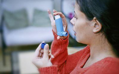 Woman using a bronchodilator, France