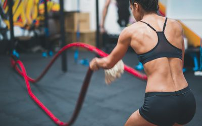 Rear View Of Female Athlete Exercising Battle Rope In Gym
