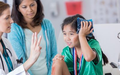 A white female ER doctor examining a young Asian female child holding an ice pack against her head.