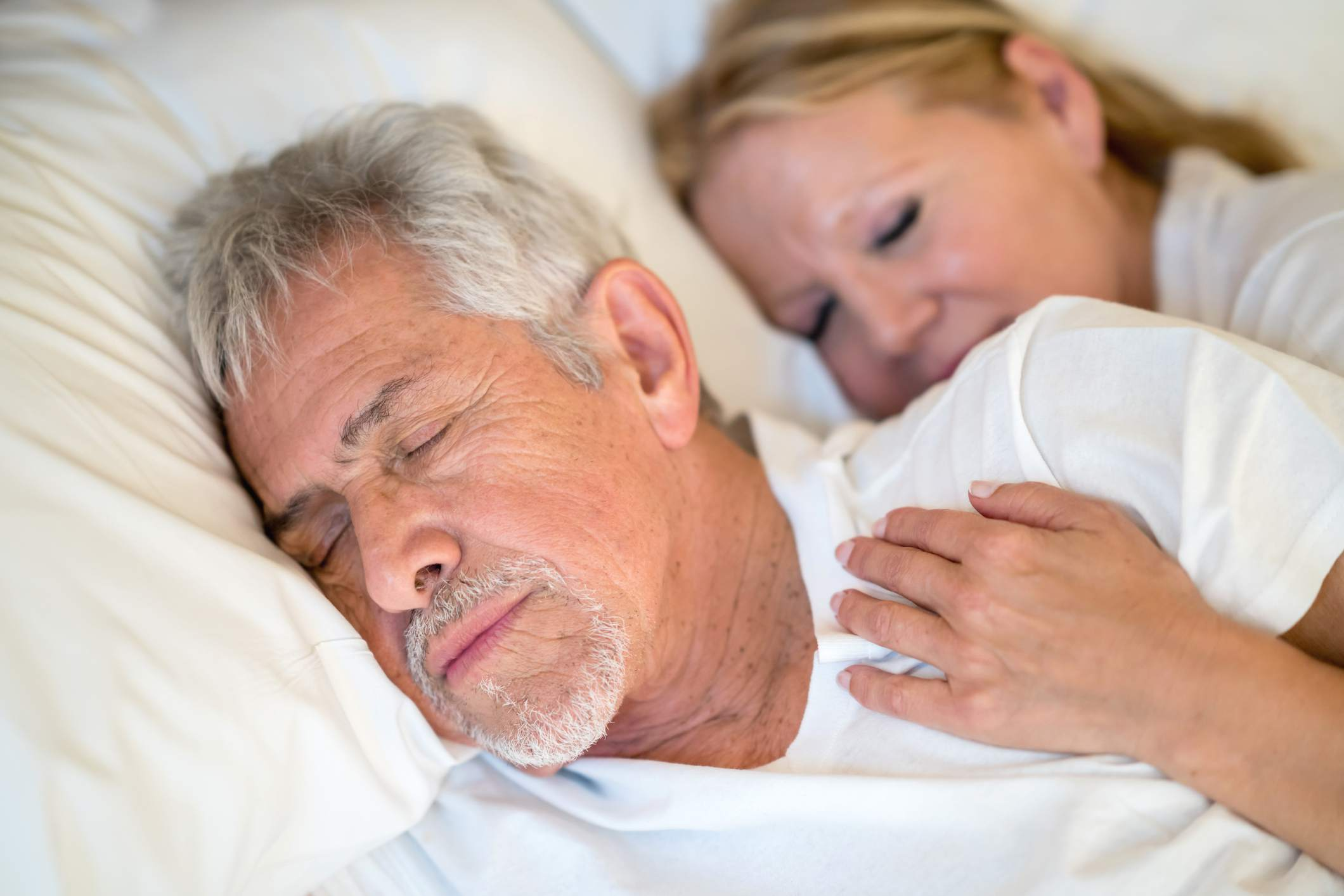 Sweet senior couple sleeping in bed and woman hugging him